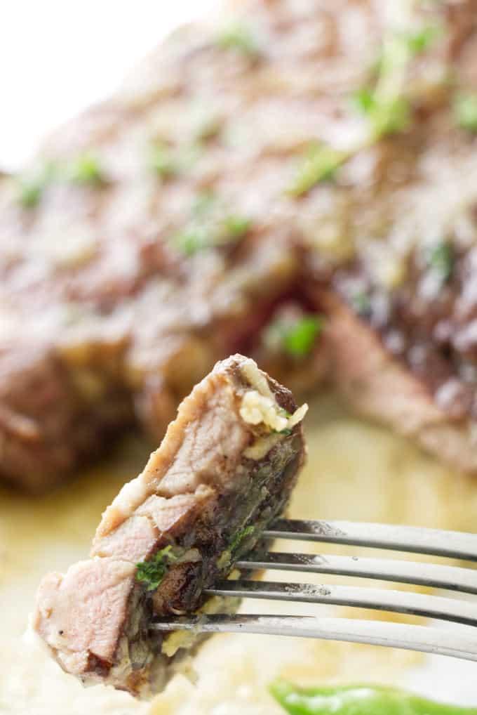 A closeup photo of a bite of a thin cut pork chop.