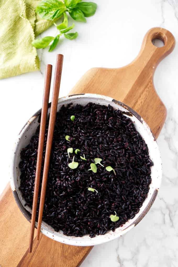 Black rice in a bowl with chopsticks on the side.