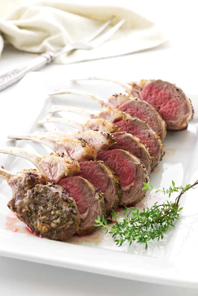 Roasted rack of lamb sliced into individual servings and placed on a serving plate.