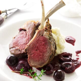 Lamb with red wine cherry sauce on a plate with mashed potatoes.