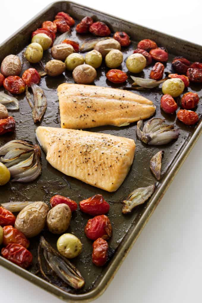 Two fillets of baked arctic char on a sheet pan with vegetables.