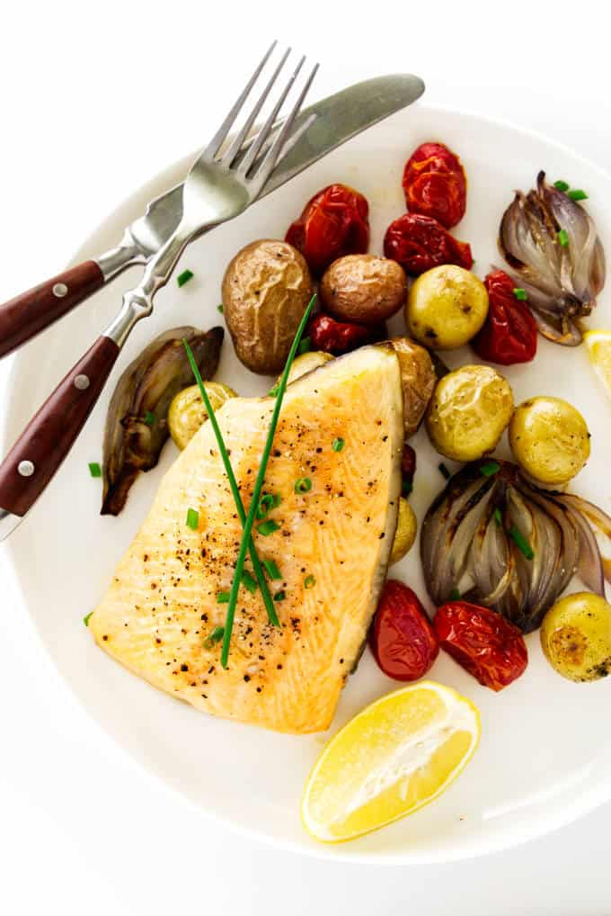 Baked arctic char with vegetables on a plate with a fork and knife.