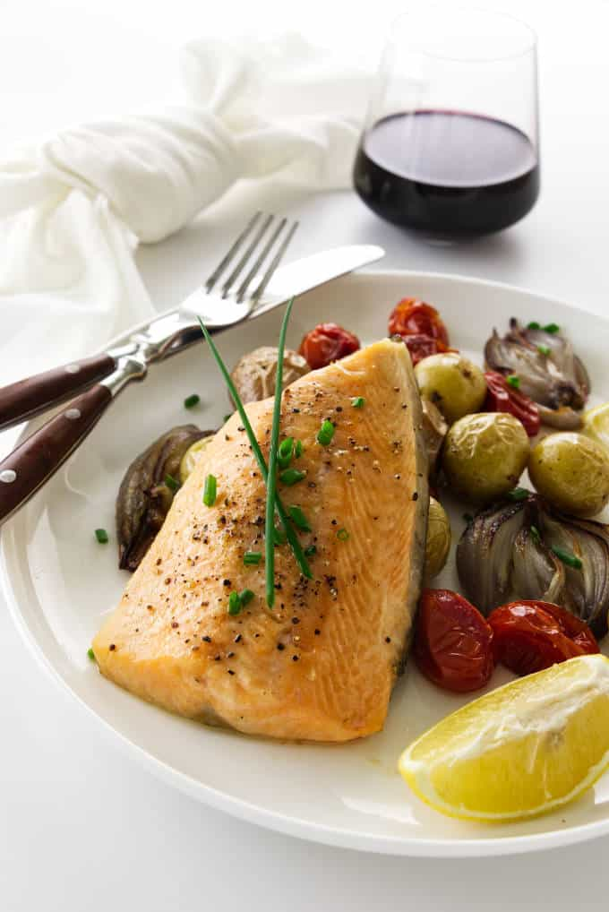 An arctic char fillet on a plate with roasted veggies and a glass of wine in the background.