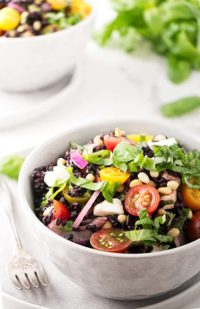 A bowl of black rice salad with tomatoes and basil.