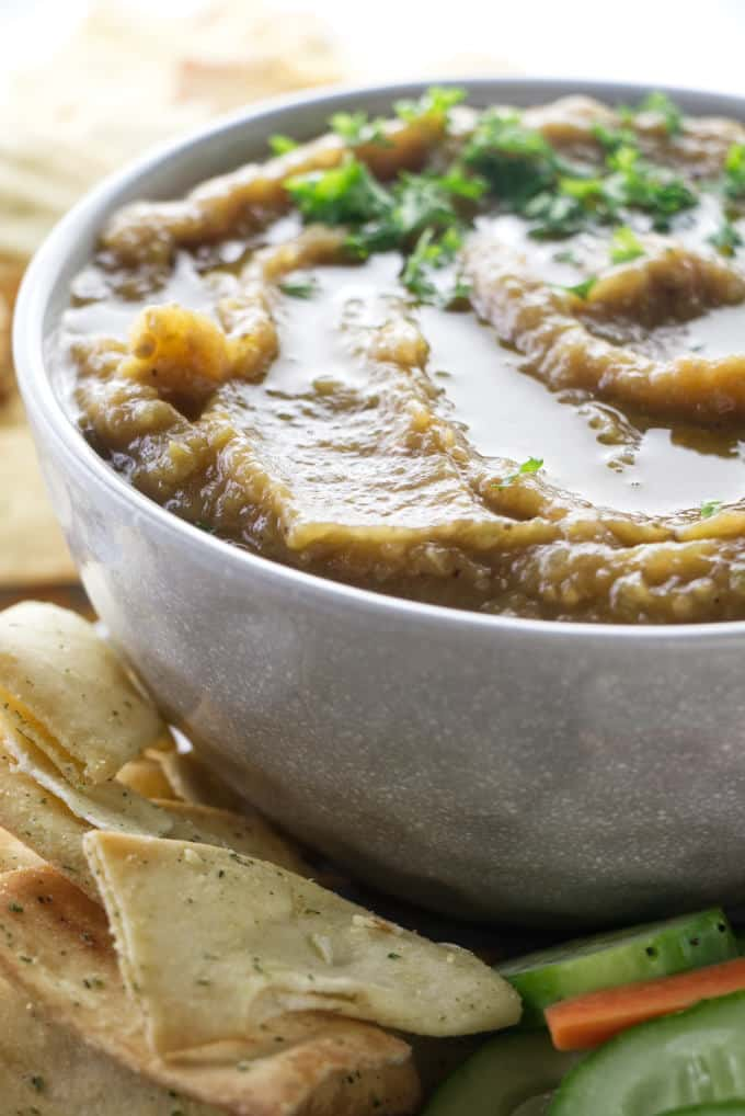 A bowl of eggplant caviar with crackers on the side.