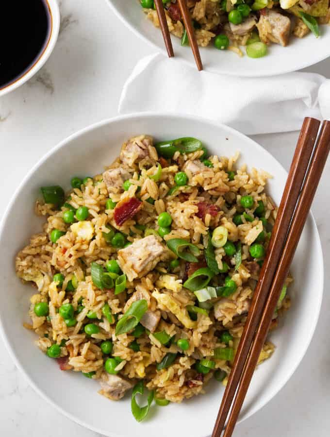 Two bowls of pork fried rice with chopsticks.