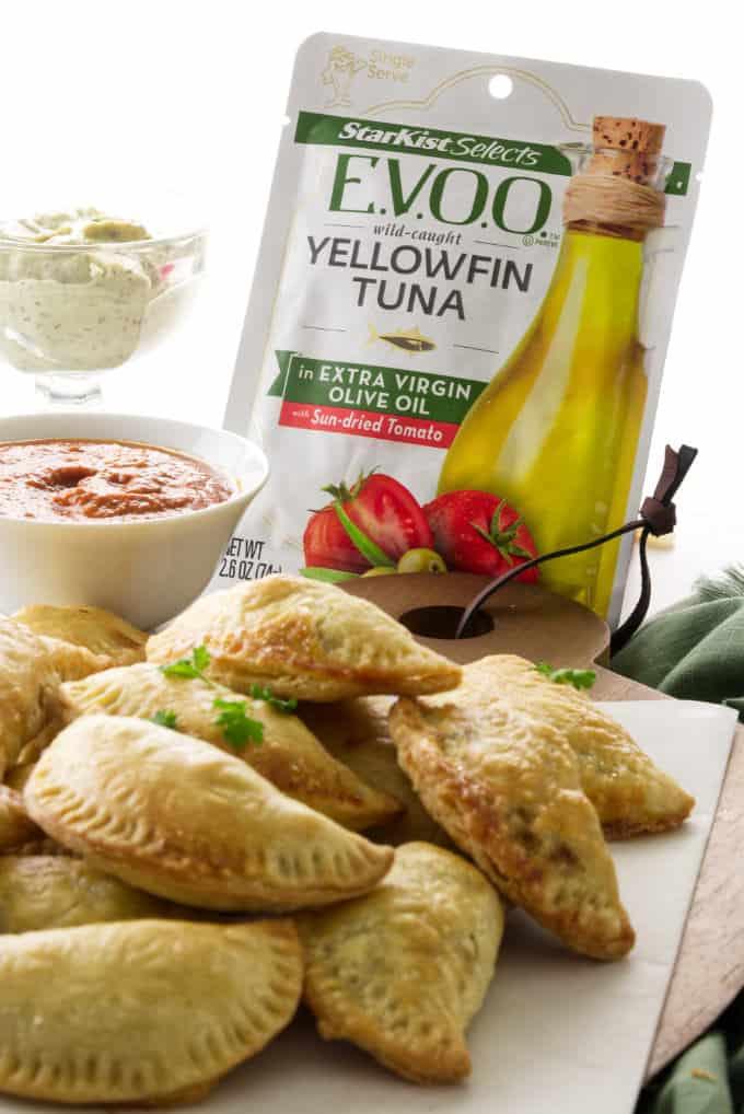 Close up shot of tuna empanadas and a pouch of Tuna empanadas with two bowls of dip and a pouch of StarKist E.V.O.O.™ tuna.