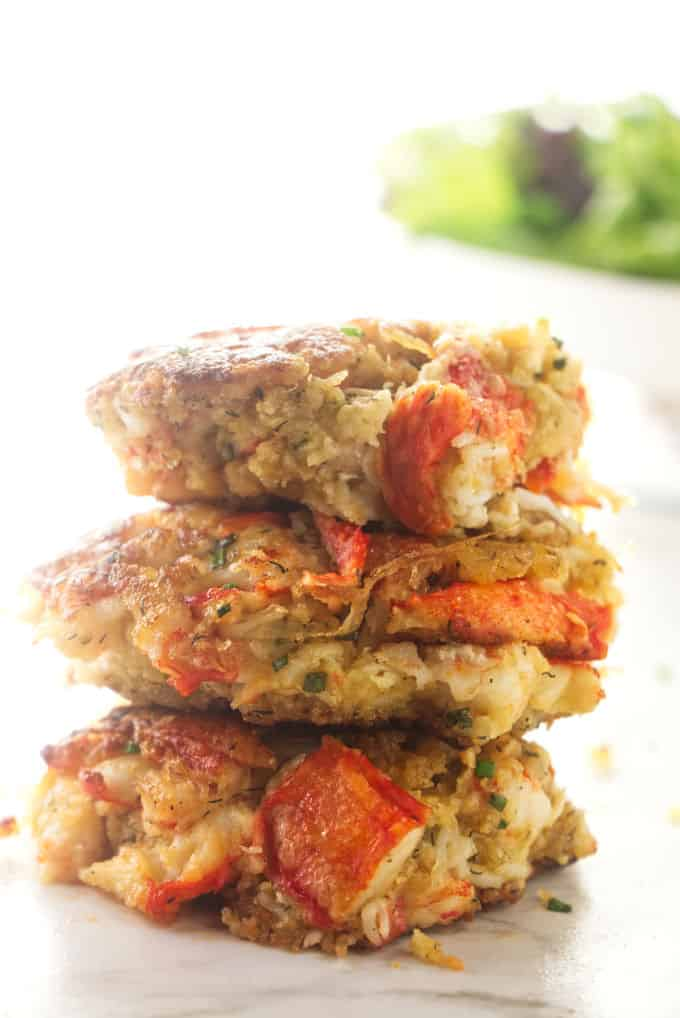 Three Alaskan King crab cakes stacked on top of each other.