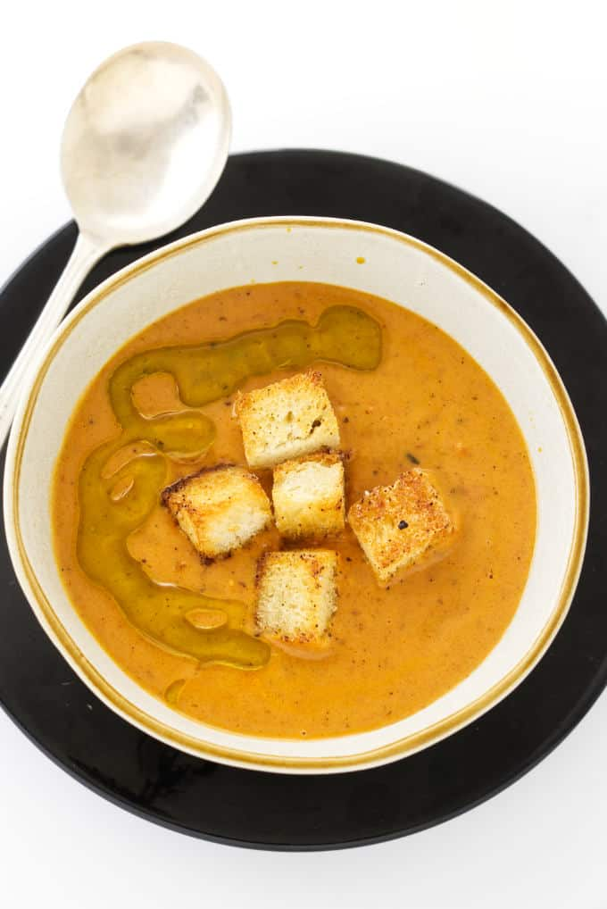 Overhead photo of Fire-Roasted Tomato Bisque with croutons and olive oil on top.