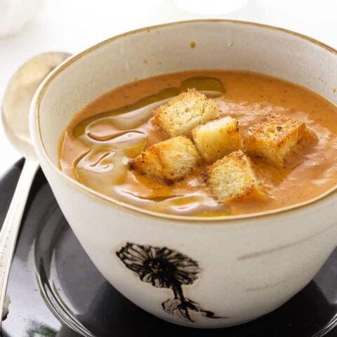 A bowl of Fire-Roasted Tomato Bisque with croutons on top.