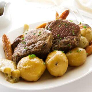 A serving platter of pork chop pot roast dinner.