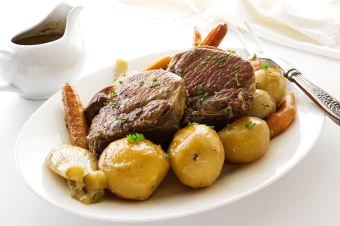 A serving platter of pork chop pot roast dinner.