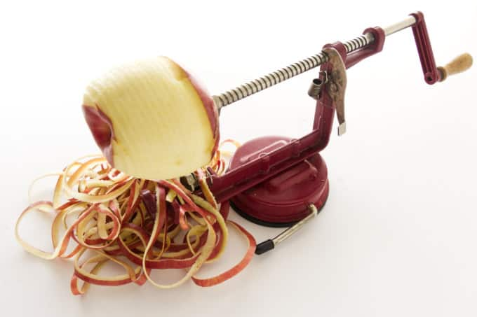 An apple on a apple-peeler with apple peels on the counter.