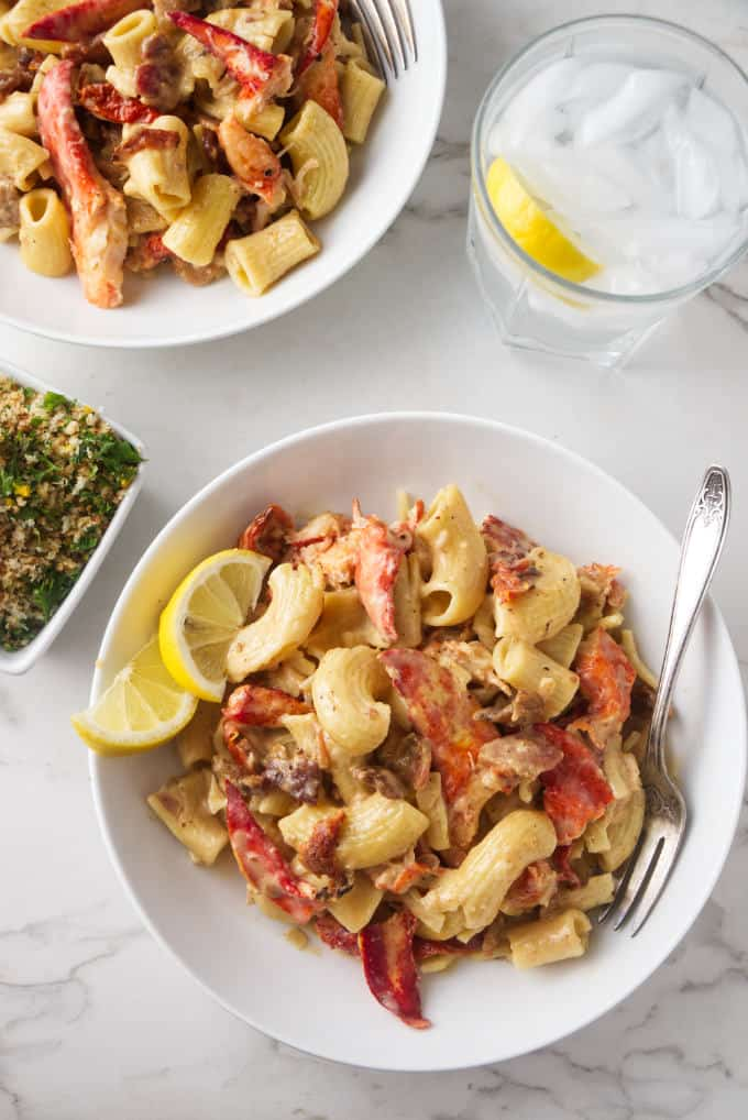 Overhead photo of 2 bowls with lobster pasta, a glass of water and crispy panko bread crumbs with lemon and garlic.