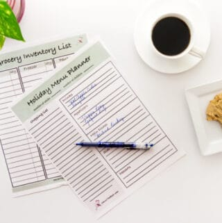 A holiday menu planner on a desk with coffee and a cookie and a pen.