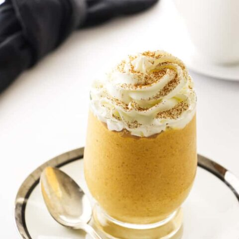 a glass filled with pumpkin mousse and whipped cream on top.