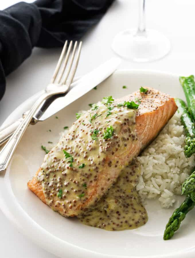 A King salmon fillet with mustard sauce on a plate with rice and asparagus.