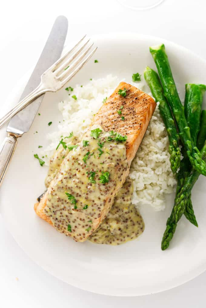 Salmon with creamy mustard sauce on a bed of rice.