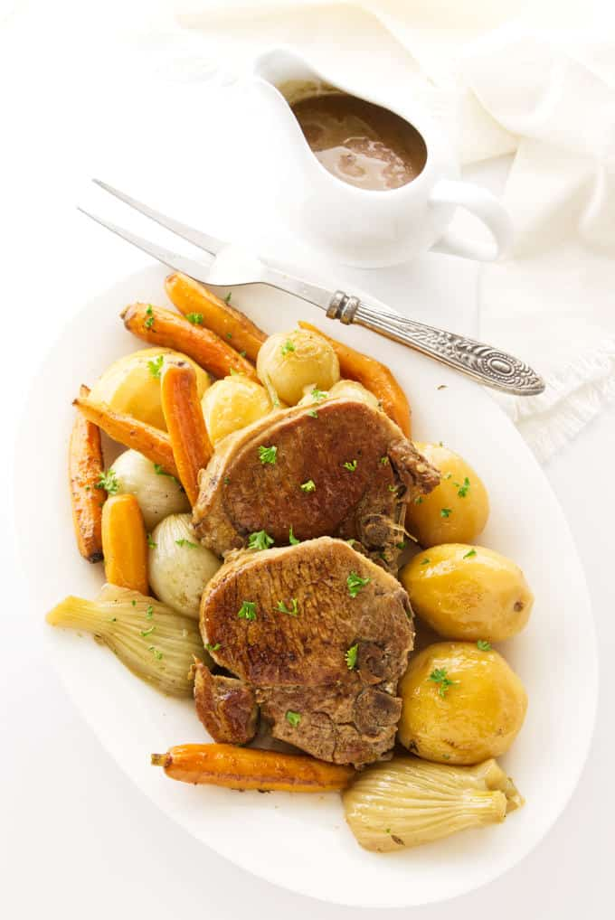 Two pork chops and veggies on a serving platter with a dish of gravy on the side.