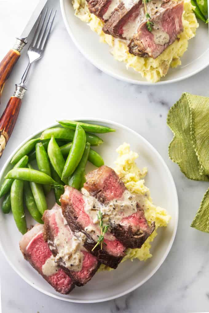 Two plates of bison ribeye steak with mashed potatoes and snap peas.