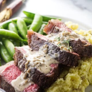 Bison ribeye steak on a bed of mashed potatoes.