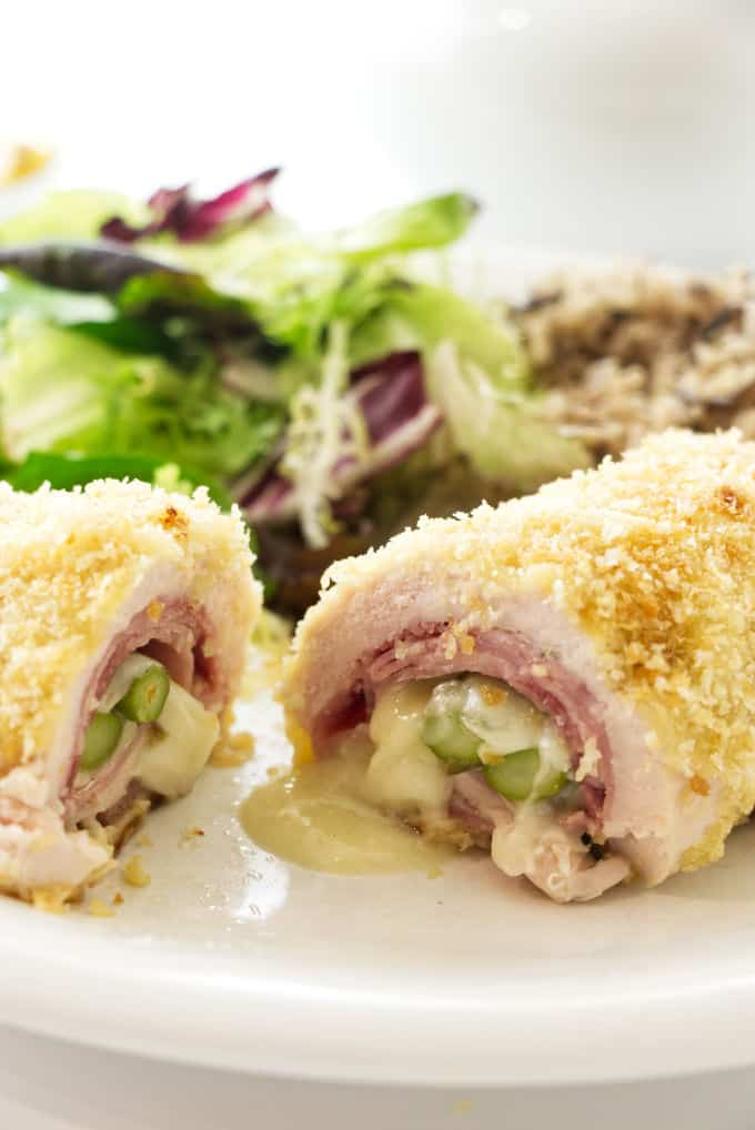 Chicken rolled up with ham, cheese, and asparagus then sliced open to see the inside