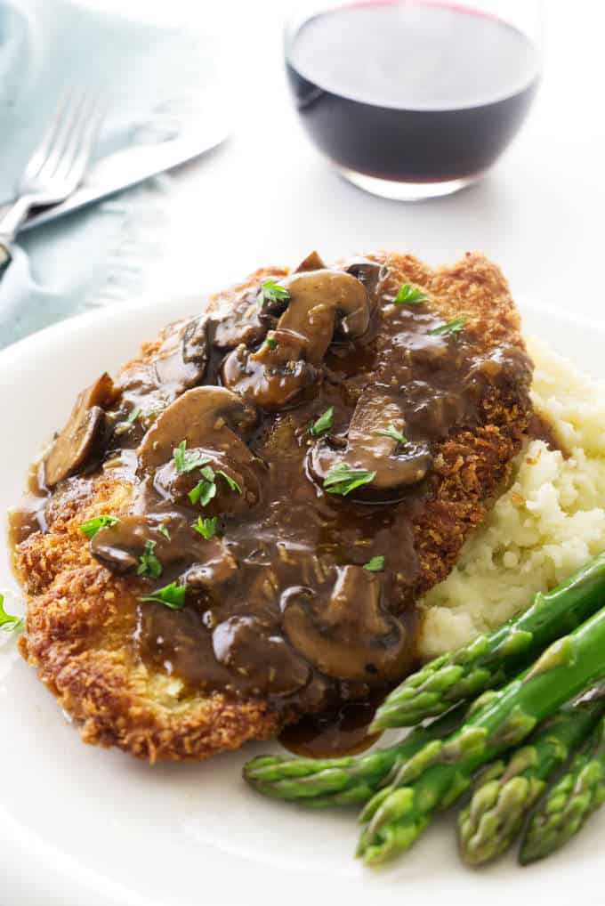 A close up of Jaeger Schnitzel and mushroom sauce on a plate with asparagus.