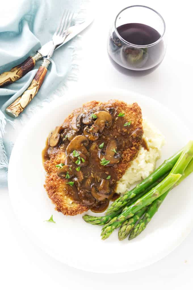 Jaeger Schnitzel and mushroom sauce on a plate with asparagus.