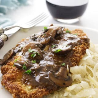 Jaeger Schnitzel and mushroom sauce on a plate with red wine in the background