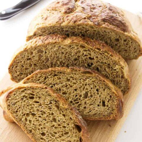 No-knead rye bread slice on a cutting board.