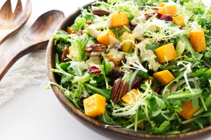 A large serving bowl of roasted butternut squash green salad