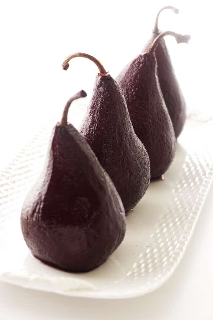 Four red wine poached pears on a serving platter.