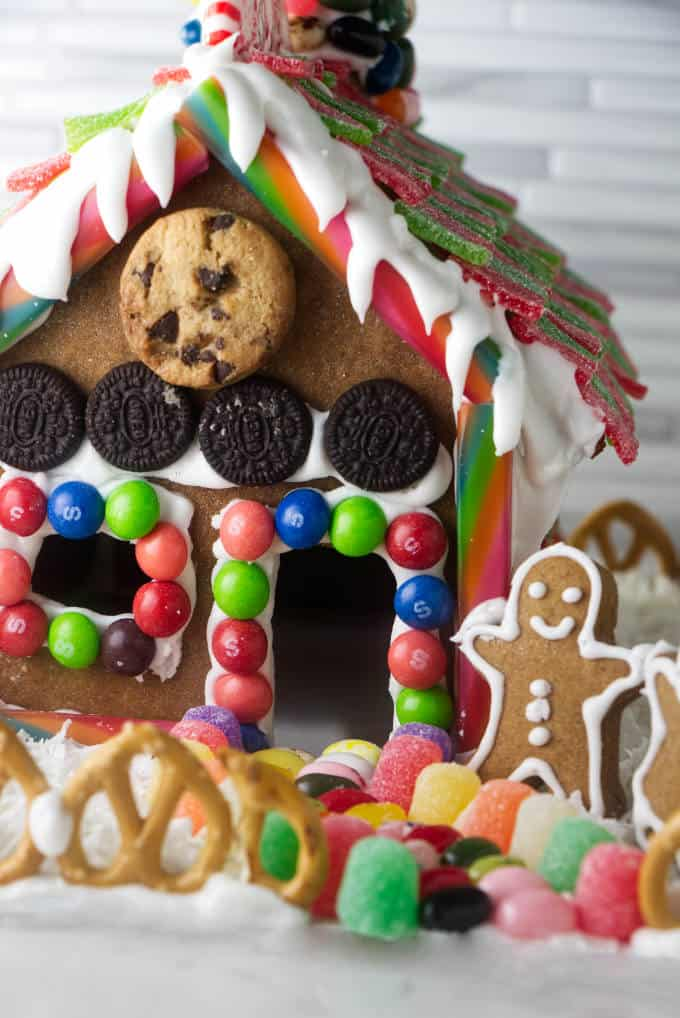 The front of a decorated gingerbread house with a gingerbread man next to it.