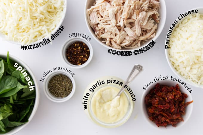 Ingredients used to make chicken spinach pizza with white garlic pizza sauce.