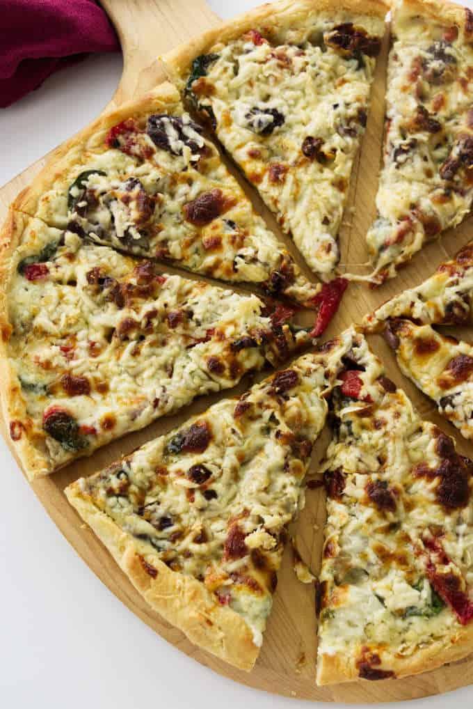 A freshly baked mushroom pizza sliced on a pizza peel.