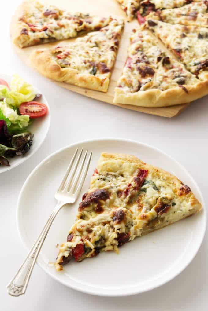 A slice of mushroom pizza next to a garden salad.