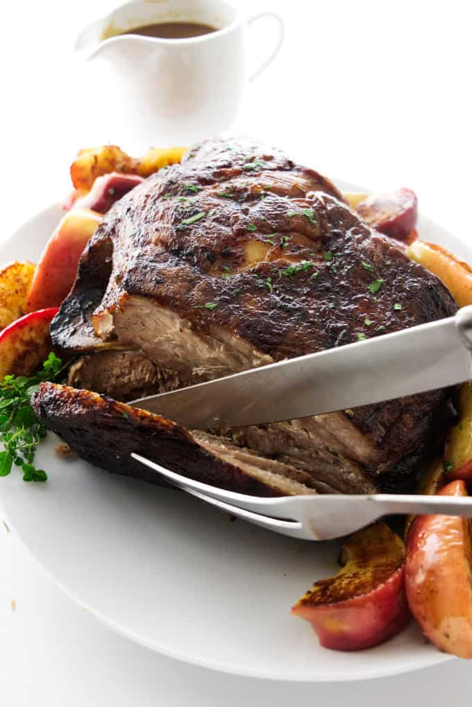 A serving of pork roast being sliced and apples next to the roast.