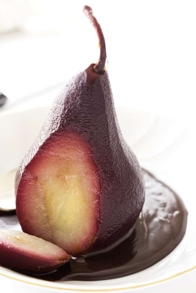 A red wine poached pear with a slice through it to show the contrasting fruit on the inside.
