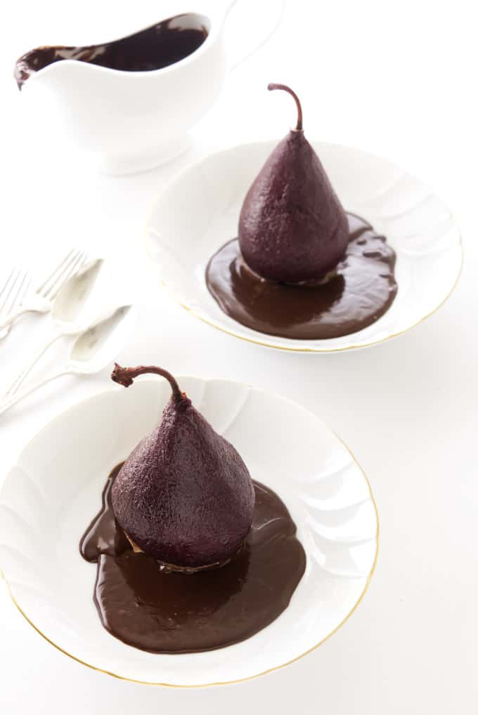 Two red wine poached pears in individual serving plates with chocolate sauce