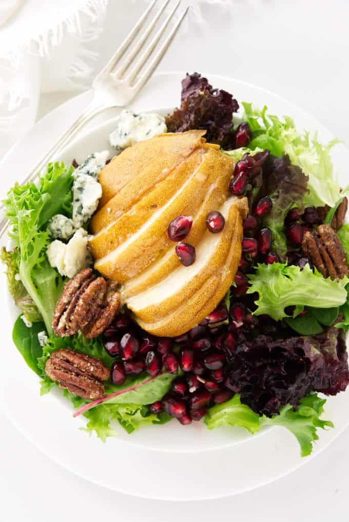 A serving of pomegranate and pear salad with blue cheese and candied pecans.
