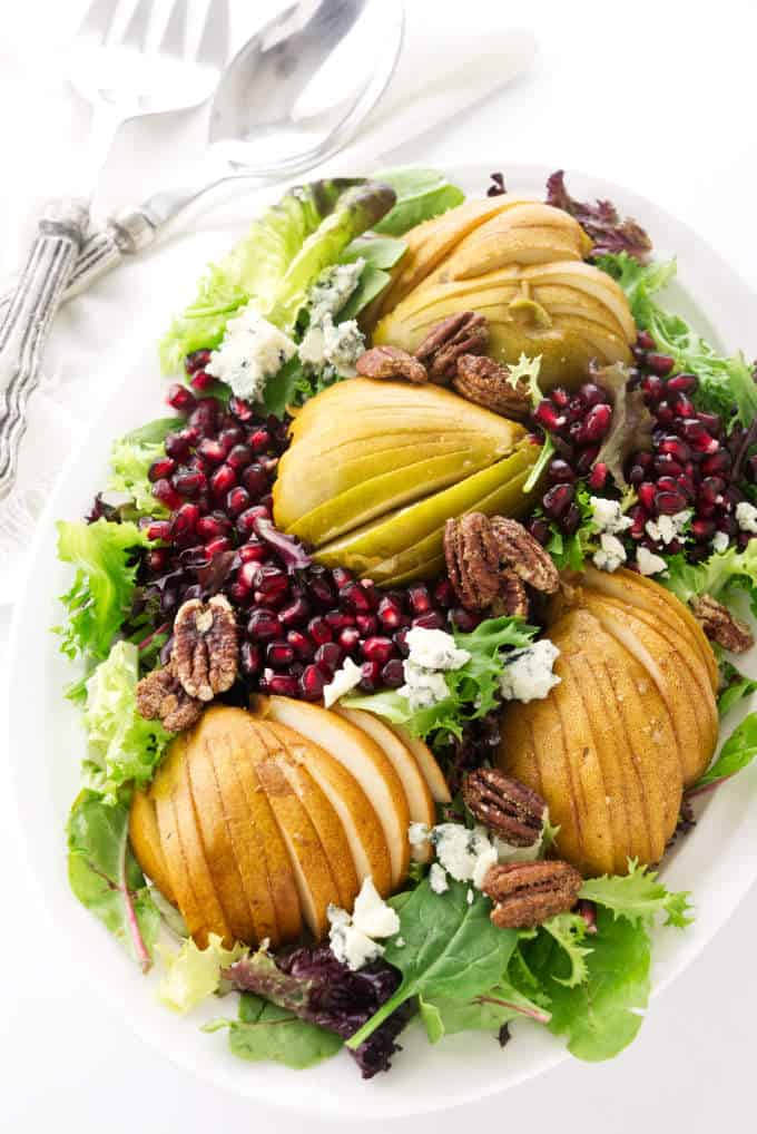 Pomegranate pear salad with blue cheese on a large serving platter.