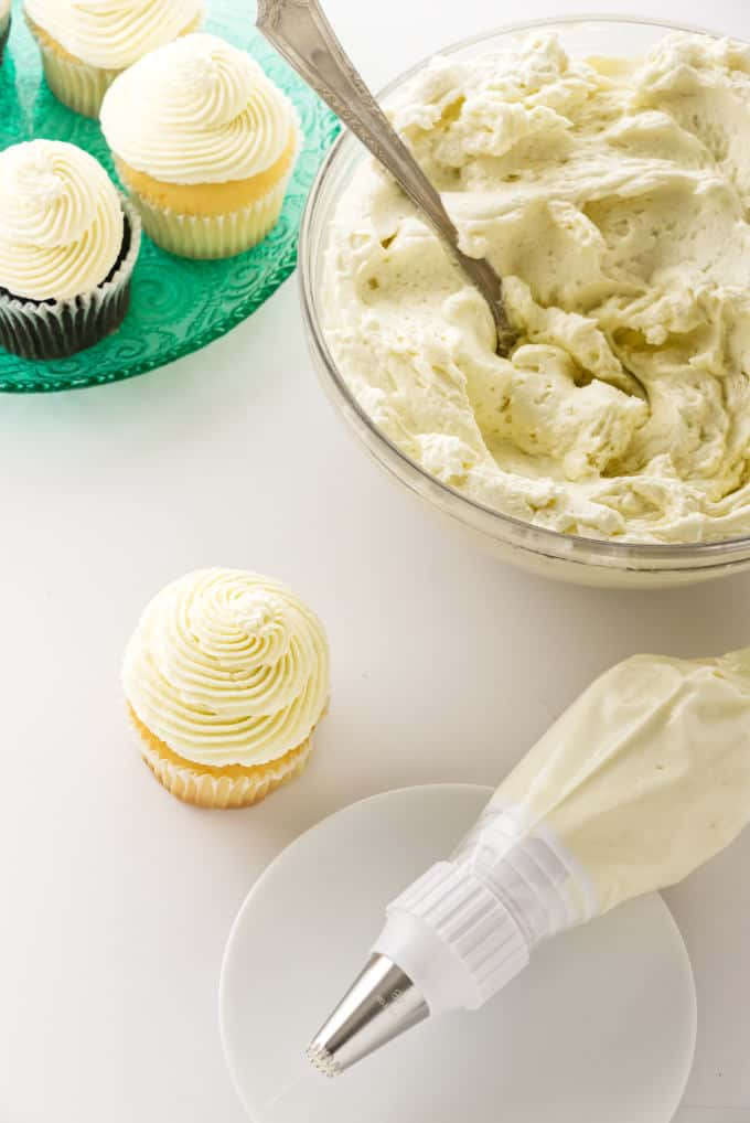 Cooked flour ermine frosting in a bowl next to some cupcakes and a piping bag.