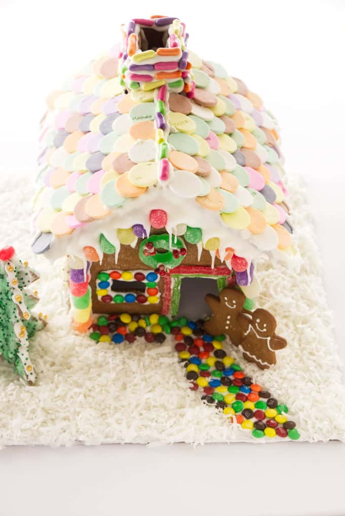 A decorated gingerbread house with a necco wafer roof and coconut flakes for snow.