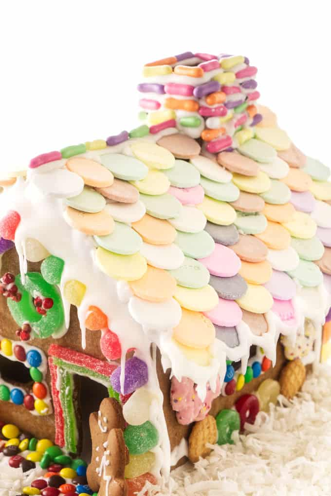 A decorated gingerbread house with necco wafers on the roof.