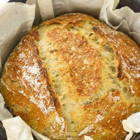 No-knead rosemary bread in a Dutch oven with parchment paper.