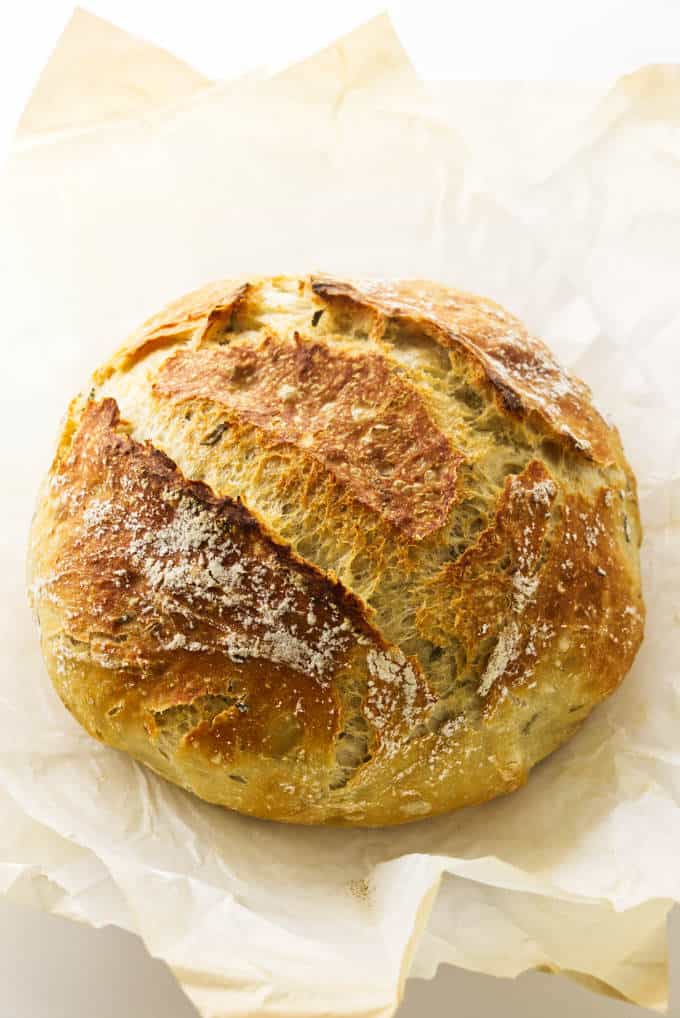 A freshly baked loaf of no knead rosemary bread on a sheet of parchment paper.