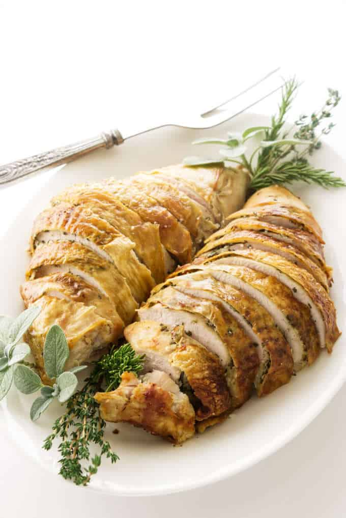 A sliced turkey breast on a serving platter with herbs.