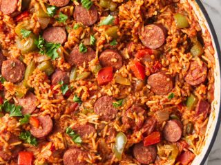 A large skillet filled with a sausage and rice one dish dinner.