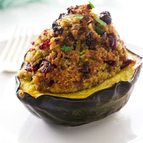 A sausage stuffed acorn squash with the stuffing piled high on the squash.