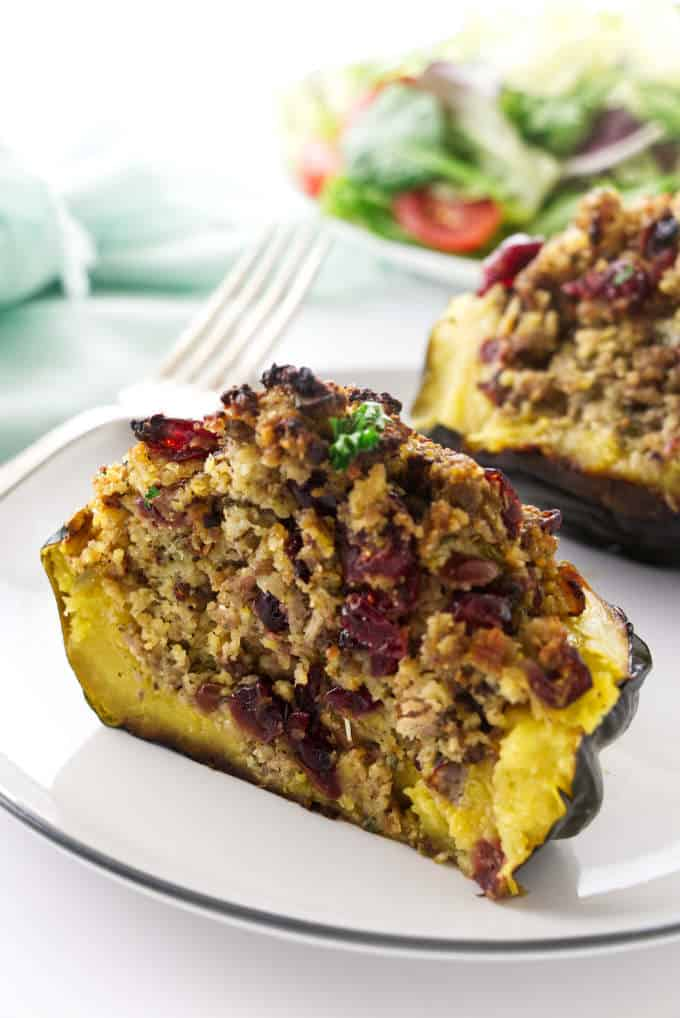 Sausage stuffed acorn squash sliced in half and showing the filling.